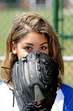 Beautiful biracial female softball player. Portrait of beautiful young woman in blue and white baseball shirt peering over glove royalty free stock image