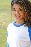 Beautiful biracial female softball player. Portrait of smiling, beautiful young woman in blue and white baseball shirt stock image