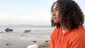 Biracial African American girl teenager young woman wearing orange hoodie, drinking takeout coffee by a harbor looking happy stock video footage