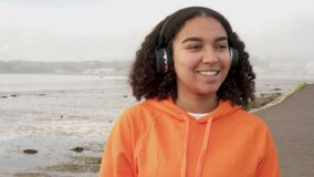 Beautiful biracial mixed race African American girl teenager walking by a harbor and listening to music on wireless headphonesi stock video footage