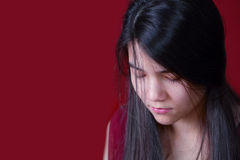 Beautiful, biracial teen girl looking down, depressed or sad, on. Red background Royalty Free Stock Photo