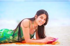 Beautiful biracial teen girl lying on tropical beach with phone Stock Images