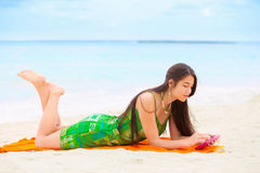 Beautiful biracial teen girl lying on tropical beach with phone Royalty Free Stock Images