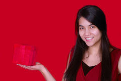 Beautiful biracial teen girl in red dress holding red present on Stock Image