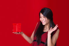 Beautiful biracial teen girl in red dress holding red present on Royalty Free Stock Photography