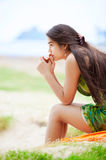 Beautiful biracial teen girl sitting at tropical beach, praying Stock Photo