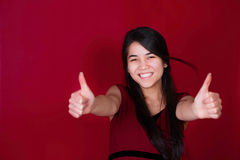 Beautiful biracial teen girl thumbs up. Red backgrou Stock Images