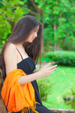 Beautiful biracial teen girl using cellphone with greenery in ba. Beautiful biracial Asian Caucasian teen girl using cellphone with greenery in background, side Stock Photography