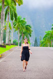 Beautiful biracial teen girl walking along palm tree lined road. In elegant black sundress in tropical setting, Hawaii Royalty Free Stock Photography