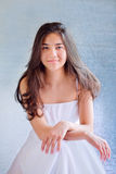 Beautiful biracial teen girl in white dress, sitting arms crosse. D at knees Royalty Free Stock Photo