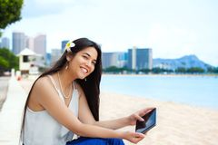 Biracial teen girl on beach using tablet computer, Waikiki, Hono Royalty Free Stock Photos