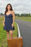 Beautiful biracial woman sitting on suitcase by road Stock Photography