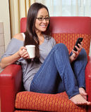 Beautiful biracial woman with smart phone. A stunning young biracial woman (Caucasian and Asian) smiles as she holds a mug of coffee while reading a text message stock photos