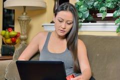 Beautiful Biracial woman using laptop computer - shopping Stock Photo