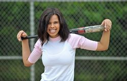 Beautiful biracial young female softball player. Stunning young biracial (African American and Caucasian) woman softball player. Holding bat over both shoulders stock photography