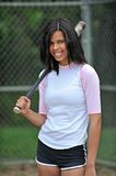 Beautiful biracial young female softball player. Stunning young biracial (African American and Caucasian) woman softball player. Holding bat on shoulder royalty free stock images