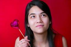 Beautiful biracial young teen girl holding heart balloon, smilin Royalty Free Stock Photography