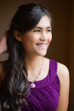 Beautiful biracial young woman in purple dress smiling off to si Royalty Free Stock Image