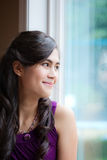 Beautiful biracial young woman smiling by window Stock Image