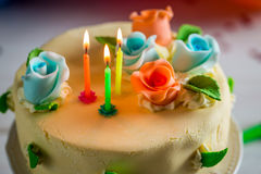 Beautiful birthday cake with lighted candles and marzipan roses Royalty Free Stock Image