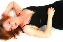 Beautiful In Black. Portrait of beautiful woman in black dress lying on white floor Stock Images