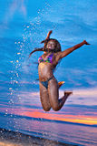 Beautiful black African American woman jumping on the beach  Stock Photo