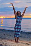Beautiful black African American woman posing on the beach at su Royalty Free Stock Image
