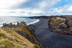 View of a Black Volcaninc Beach Fro the Top of a Cliffin Iceland. Beautiful Black Beach in Iceland on a Cloudy Autumn Day. Two People are Visible on the Beach stock photos