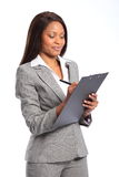 Beautiful black business woman with clipboard. Smiling young beautiful business woman wearing grey suit, writing on a clipboard stock images