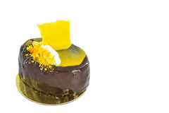 Beautiful black chocolate cake with yellow decorations, siting on golden plate Royalty Free Stock Photography