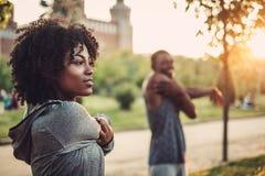 Black couple doing exercise outdoors. Beautiful black couple doing exercise outdoors stock images