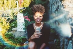 Brazilian young female taking selfie while sitting in park. Beautiful black curly girl is photo messaging with her boyfriend via smartphone and sending him Royalty Free Stock Image