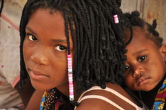 Beautiful black girl with sister on her back in Mozambique. With traditional african hair style Royalty Free Stock Photography