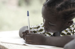 Beautiful black girl writing and learning activity with a blue p. Cute African schoolgirl doing her homework at school: beautiful black girl writing and learning Stock Image