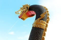 Beautiful Black and Gold colors of Praya Nark or Naga in Thai temple with colorful sky and sun flare effect on sunrise time Royalty Free Stock Photo