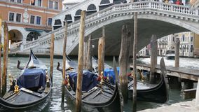 Beautiful black gondolas with gilded figures stand parked under a world famous Rialto Bridge. Beautiful black gondolas with gilded figures stand parked under the stock footage
