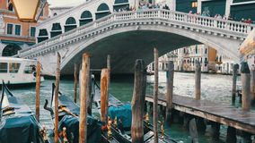 Beautiful black gondolas with gilded figures stand parked under a world famous Rialto Bridge. Beautiful black gondolas with gilded figures stand parked under the stock video footage