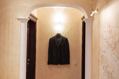 Beautiful black groom`s suit hanging on lamp near the wall Stock Photography