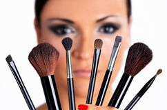 Beautiful black hair girl with makeup brushes. Stock Photo