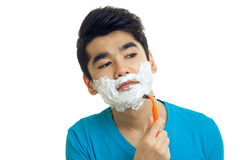 Beautiful black-haired guy with foam on his face looking sideways and shaved closeup Stock Photography