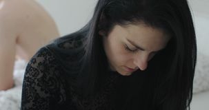 Beautiful black haired young woman feels depressed during bedroom crisis. Blond man sitting in background stock video