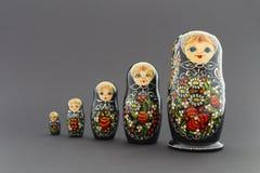 Beautiful black matryoshka dolls. Beautiful black russian nesting dolls & x28;matryoshka& x29; with white, green and red painting in front of dark background Stock Photo
