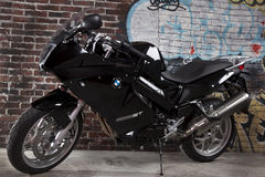 Beautiful black motorcycle. Beautiful new black motorcycle against a brick wall Royalty Free Stock Photo