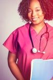 Beautiful Black Nurse. Beautiful black smiling nurse holding file Stock Image