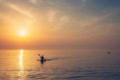 Beautiful Black sea sunrise in Odessa with silhouette of kayaking man and warm colors royalty free stock photos
