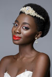 Beautiful black skin bride. Beautiful black skin young woman with red lips in white gown and pearl tiara. Beauty shot on grey background. Copy space Royalty Free Stock Image