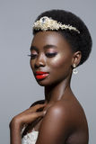 Beautiful black skin bride. Beautiful black skin young woman with red lips in white gown and pearl tiara. Beauty shot on grey background. Copy space Stock Photo