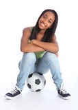 Beautiful black soccer player girl sitting on ball Royalty Free Stock Image