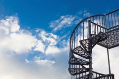 Spiral staircase against the blue sky with clouds. Beautiful black steel staircase on the background of blue sky with white clouds. Free space for text Royalty Free Stock Photo