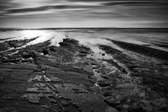 Beautiful black and white landscape of rocky shore at sunset Stock Image